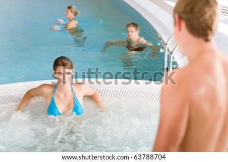 Swimming pool - young attractive couple relax in hot tub - stock photo