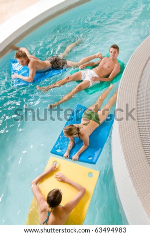 Swimming pool - young people have fun, lying on floating foam matress - stock photo