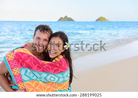 Swimming romantic couple wrapped in bathing towel on beach. Portrait of happy young interracial couple embracing each other having fun during holidays vacation travel. Asian woman, Caucasian man. - stock photo