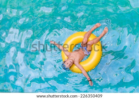 Swimming, summer vacation - lovely child boy playing in blue water (space for text) - stock photo