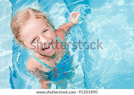 Swimming, summer vacation - lovely girl playing in blue water - stock photo
