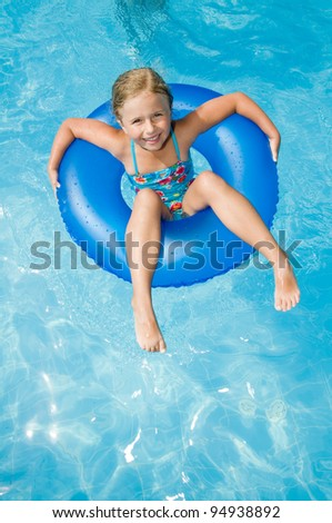 Swimming, summer vacation - lovely girl playing in blue water - space for text