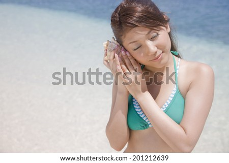 Swimsuit women hear the sound of the sea and to the ear shells