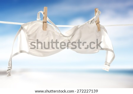 swimwear on rope and sky of blue color with sand of white color