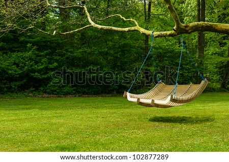 Swing bench in lush garden. Curved swing bench hanging from the bough of a tree in a lush garden with woodland backdrop for relaxing on hot summer days - stock photo