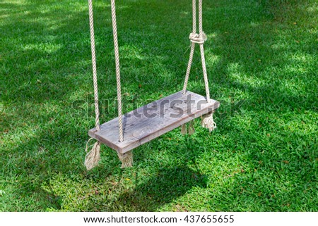 Swing hanged on a tree ,Wooden swing in the garden,wooden swing with green grass background in the park,empty swing