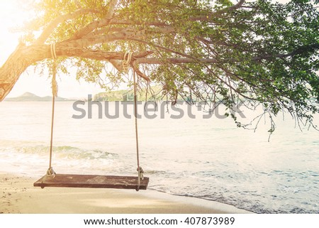 Swing hanging on tree on the island, with bright sunlight, vintage tone - stock photo