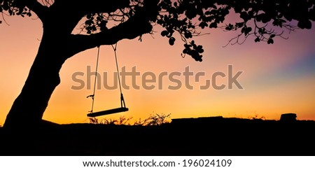 Swing in the sunset  - stock photo