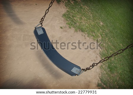 Swing on a chain over dirt and grass on a sunny day
