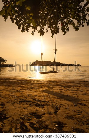 Swing on the beach at sunset background - stock photo