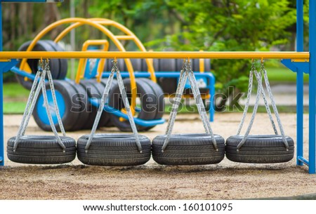 Swinging road of old tires on kids playground - stock photo