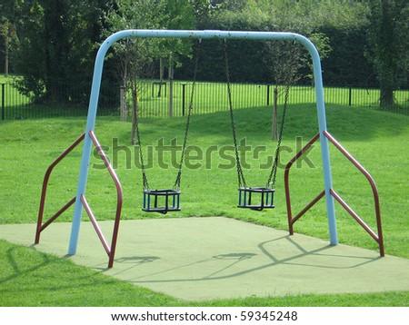 Swings in children's playground - stock photo