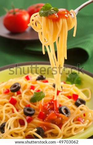 swirl of spaghetti on a fork garnished with sauce and leaf