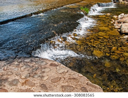 Swirl of water among the stones of a small river - stock photo