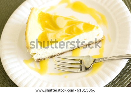 Swirled Mango Cheesecake Served on a White Plate with a Fork - stock photo