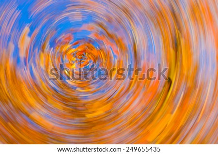 Swirling autumn color against a blue sky. The concepts are dizzying autumn discount sales or other autumn related uses.  - stock photo