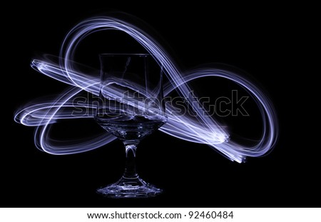 Swirling light trails dance around a glass chalice - stock photo