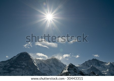 swiss alps with sun - stock photo