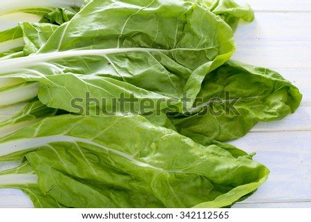 Swiss chard leaves on white painted wood - stock photo
