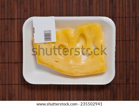 Swiss cheese packed with bar code. - stock photo