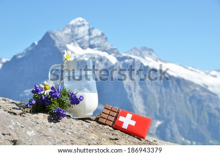 Swiss chocolate and jug of milk against mountain peak. Switzerland  - stock photo