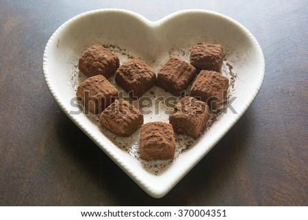 Swiss Chocolate Truffles on a Heart Shaped Plate - stock photo