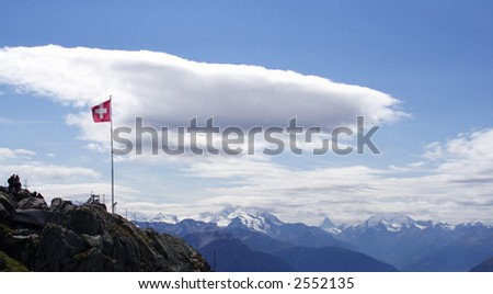 Swiss flag against a white fluffy cloud. Panoramic scenery of the swiss mountain range. - stock photo