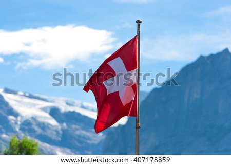 Swiss flag against Alps mountains. Horizontal shot with a selective focus - stock photo