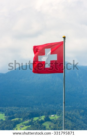 Swiss flag against Alps mountains. Vertical shot with a selective focus - stock photo