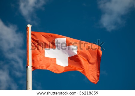 Swiss flag against blue sky - stock photo