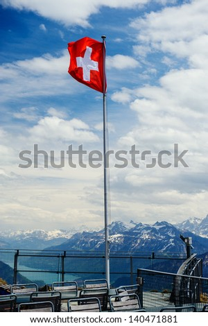 Swiss flag against mountains - stock photo