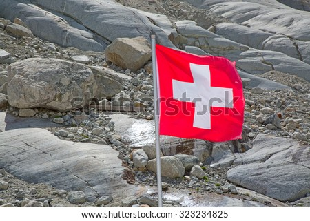 Swiss flag against rocky background - stock photo