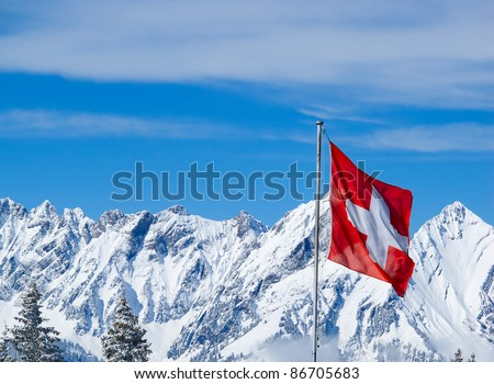 Swiss flag against snowy mountains - stock photo