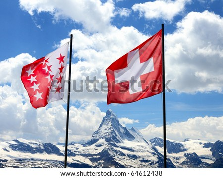 swiss flag and flag of canton Valais fly in front of mountain Matterhorn range - stock photo