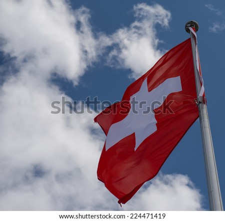 Swiss flag on a background of blue sky - stock photo