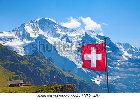 Swiss flag on the top of Mannlichen (Jungfrau region, Bern, Switzerland) - stock photo