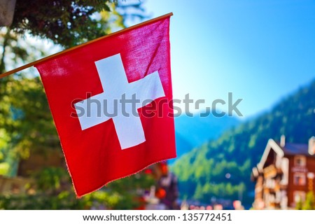 Swiss flag on town background. - stock photo