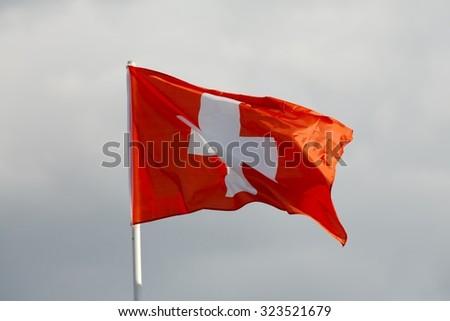 Swiss flag waving against blue sky - stock photo