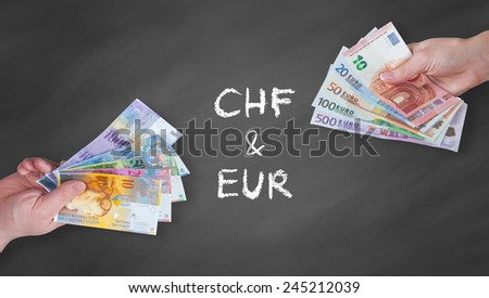 Swiss Franc and Euro banknotes on black board - stock photo