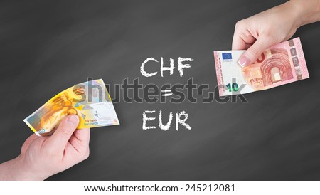Swiss Franc and Euro banknotes on black board - Swiss Franc and euro is equal - stock photo