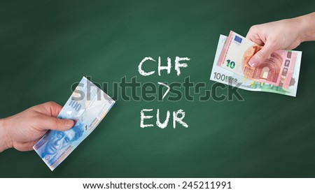 Swiss Franc and Euro banknotes on green board - Swiss Franc is stronger than Euro - stock photo