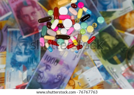 Swiss francs and tablets as a symbol of health costs - stock photo