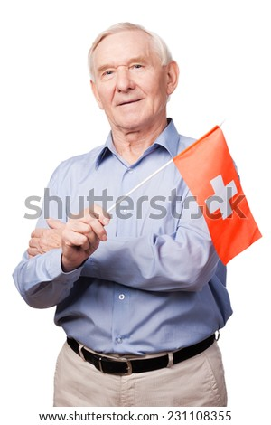 Swiss friendship. Cheerful senior man holding flag of Switzerland and smiling at camera while standing against white background - stock photo