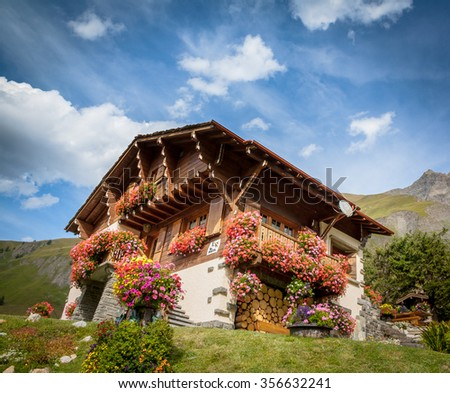 Swiss house with flowers in the Alps - stock photo