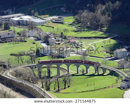 Swiss mountain train Bernina Express, circular viaduct at Brusio. Railway line for express is the highest railway in Europe, UNESCO World Heritage Site. One of the most spectacular ways to cross Alps - stock photo