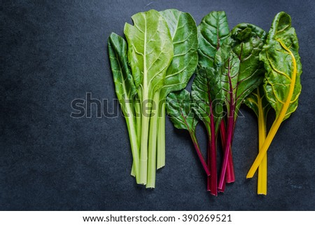Swiss rainbow chard, vibrant vegetable. Flat lay, from above on dark slate. - stock photo