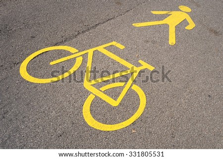 Swiss yellow road marking in Thun indicating the road is a pedestrian walkway and bicycle path at the same time. Pedestrians and bikers have to be careful and give each other some space.  - stock photo