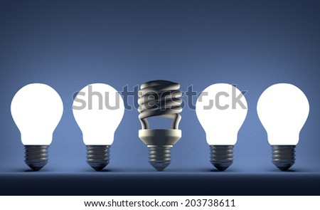 Switched off fluorescent light bulb in row of glowing incandescent ones on blue textured background
