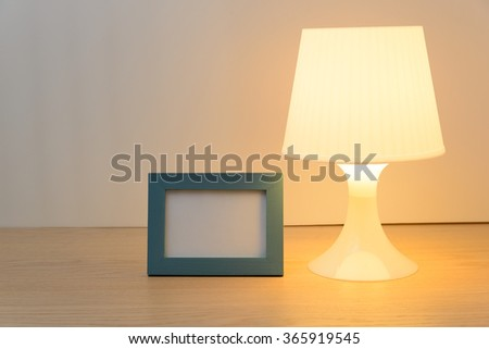 Switched on table lamp and photo frame on wooden table white background