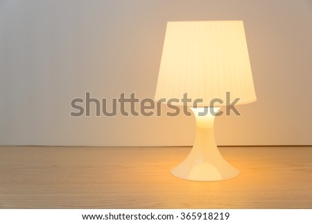 Switched on table lamp on wooden table white background